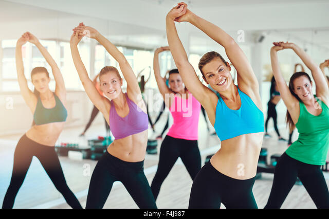 fitness, sport, training, gym and lifestyle concept - group of smiling people exercising in the gym - Stock Image