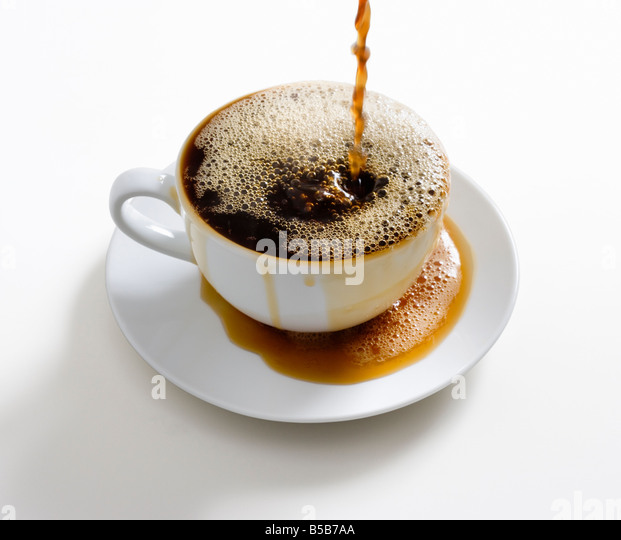 Cup of coffee overflowing - Stock Image