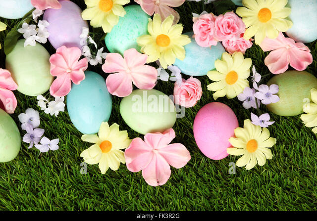 Colorful Easter eggs on grass with flowers background - Stock Image