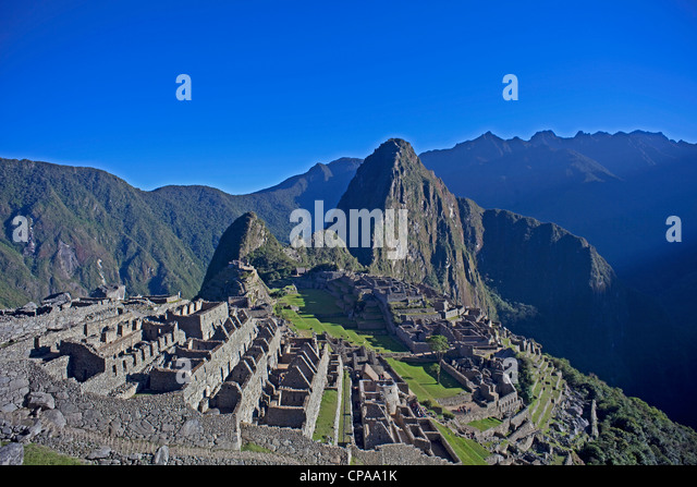 Inca ruins of Machu Picchu with Huaynu Picchu behind in the Sacred Valley of Peru at sunrise. - Stock Image