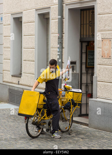 Postman delivering letters from bicycle in Regensburg, Bavaria, Germany - Stock Image