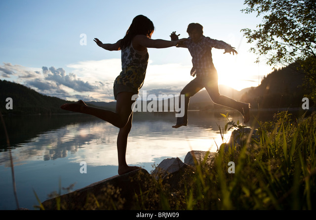 Two young adults balancing on rocks at sunset next to the lake. - Stock-Bilder
