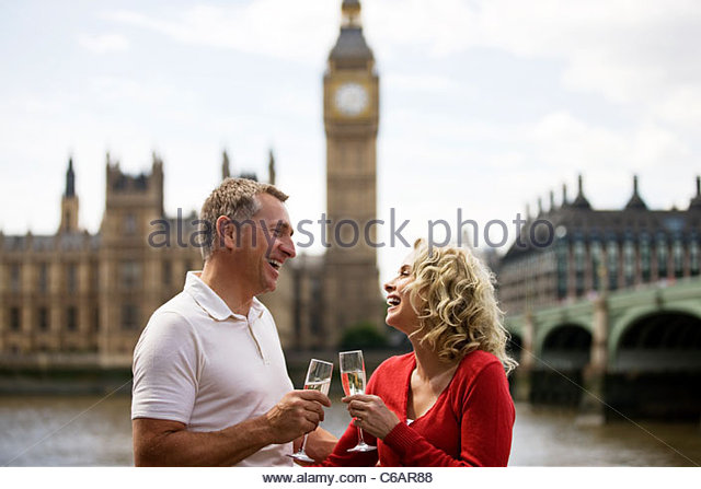 A middle-aged couple in front of the Houses of Parliament, drinking champagne - Stock Image