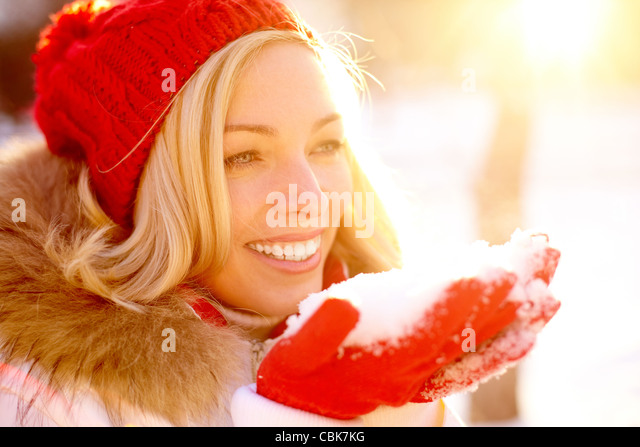 Portrait of happy girl holding snow on palms with sunshine over her - Stock Image