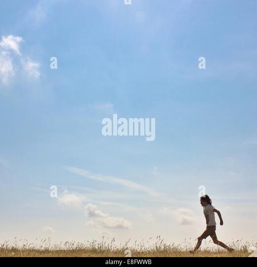 Side view of a girl running in rural landscape - Stock Image
