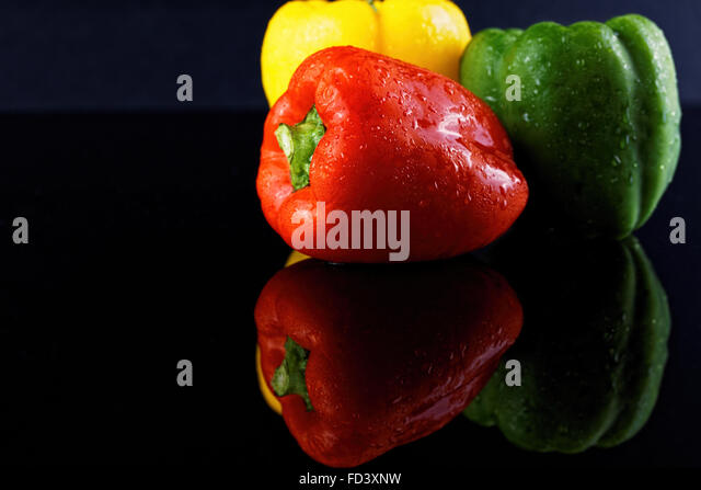 colorful peppers over dark background - Stock Image