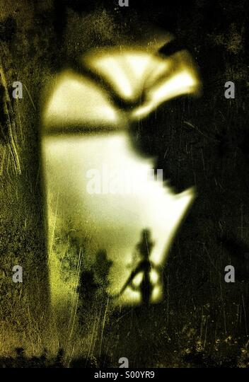 Shadow of woman holding candle stick - Stock Image