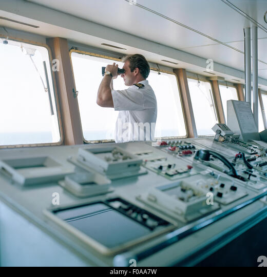 Sailor using binoculars on container ship at sea - Stock Image