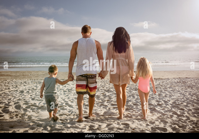 Young family holding hands together on beach, rear view - Stock-Bilder