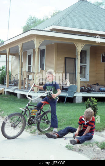 Boys together in 1970's one with a Raleigh Chopper bike standing in front of a home with no basement and a large - Stock Image