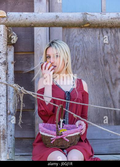 Beautiful blonde young woman basket fruit apple in hand eating eat - Stock Image