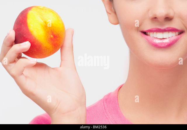 Close-up of a woman holding a peach - Stock-Bilder