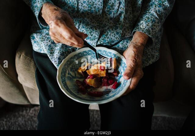 Senior woman eating a bowl of pie. - Stock-Bilder