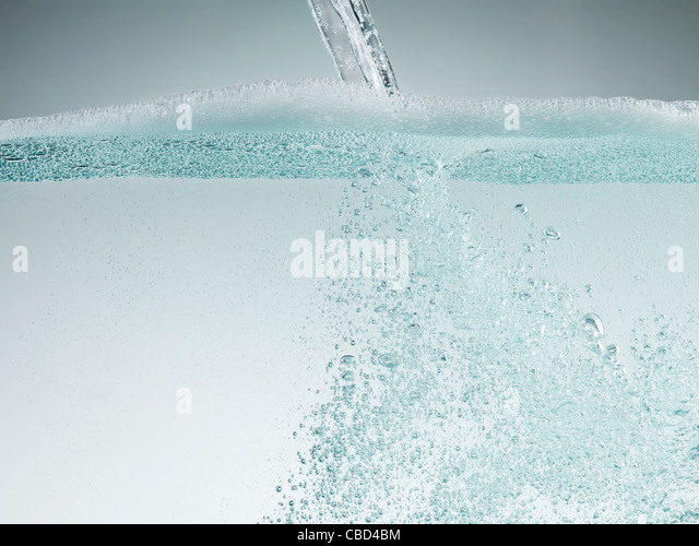 Stream pouring into soapy water - Stock Image