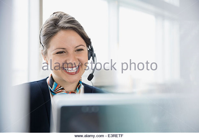 Airport customer service representative with headset at computer - Stock Image