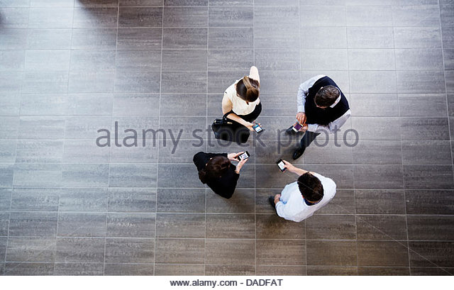 Four people using mobile phone - Stock Image
