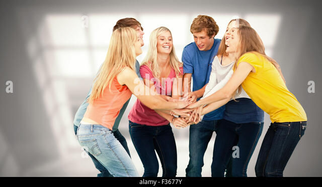 Composite image of group of friends about to cheer with their hands stacked - Stock Image