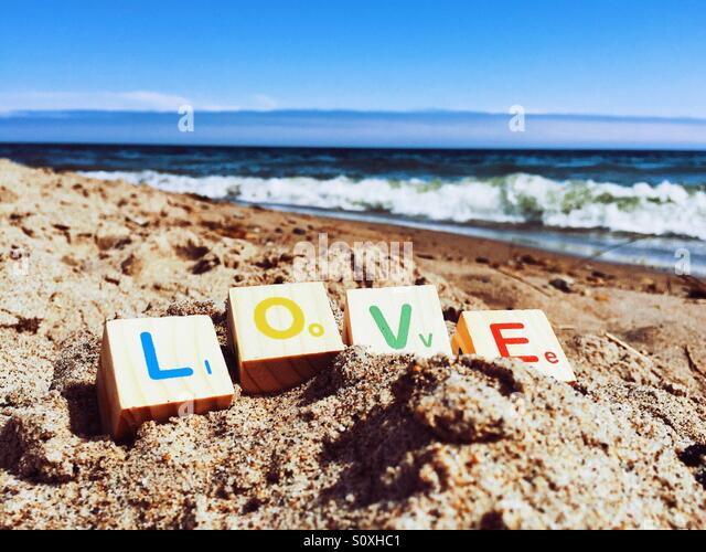 Child's blocks spelling out the word 'love' on a sandy beach - Stock Image