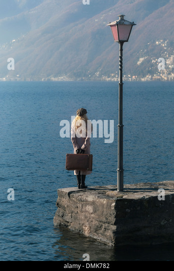 a woman in a pink coat is standing on a jetty at a lake - Stock Image