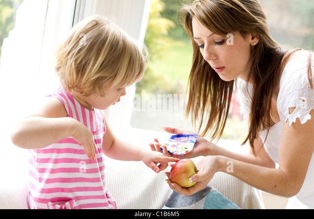 Child choosing between an apple or sweets - Stock Image