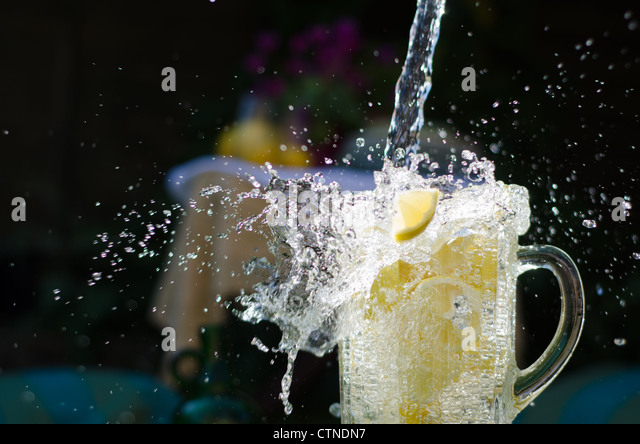 Water pouring and splahing into glass jug filled with lemons on sunny day. - Stock Image