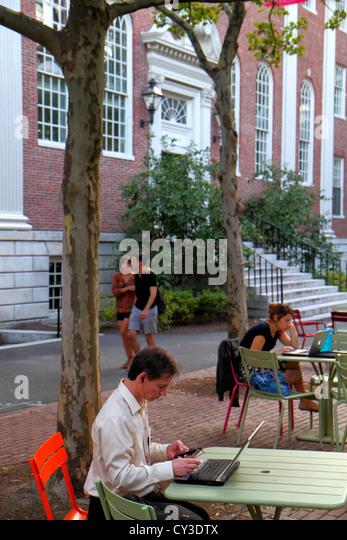 Boston Massachusetts Cambridge Harvard University campus man student sitting laptop computer couple woman - Stock Image