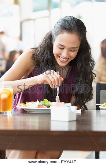 Mixed race woman eating lunch in cafe - Stock Image