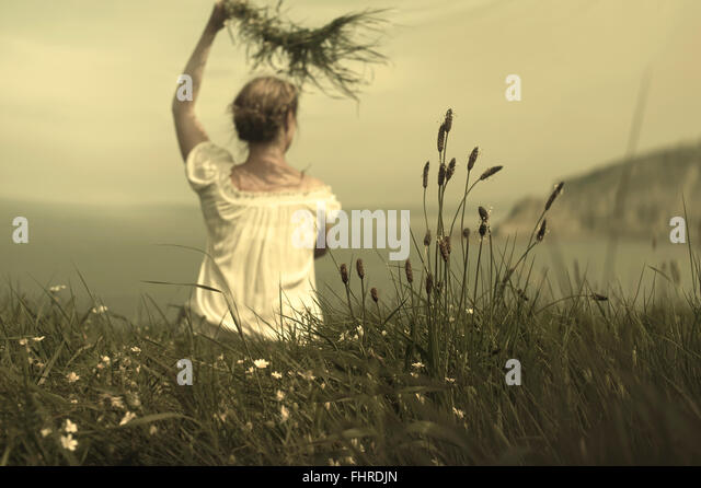 young woman sitting on cliff waving and holding grass awaiting her lover - Stock-Bilder