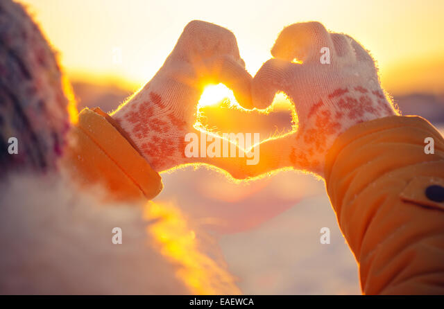 Woman hands in winter gloves Heart symbol shaped Lifestyle and Feelings concept with sunset light nature on background - Stock-Bilder