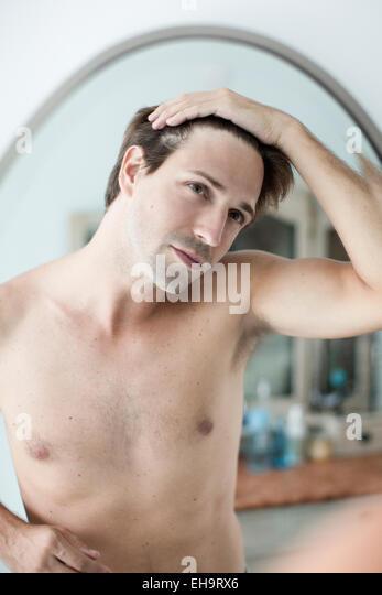 Man scrutinizing hairline in mirror - Stock-Bilder