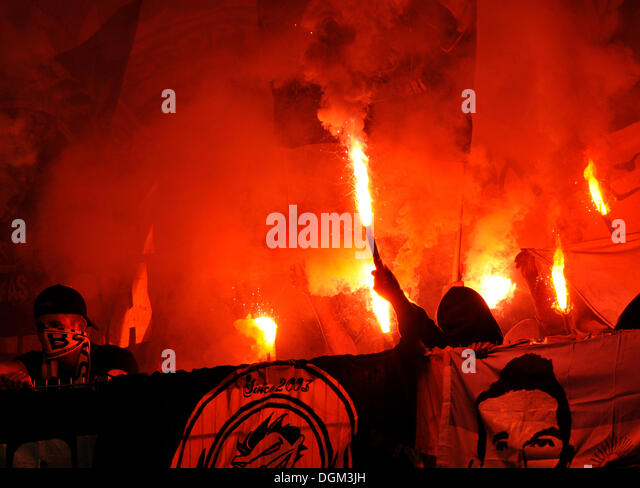 Violent, masked supporters igniting flares in a stadium fan block - Stock Image