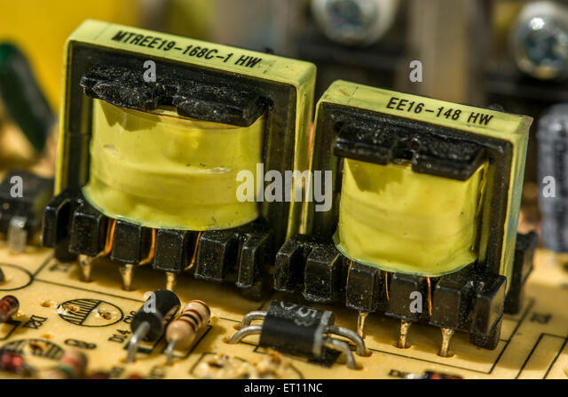 Macro-photo of two small transformers on a desktop PC power unit (PSU) circuit board. - Stock Image