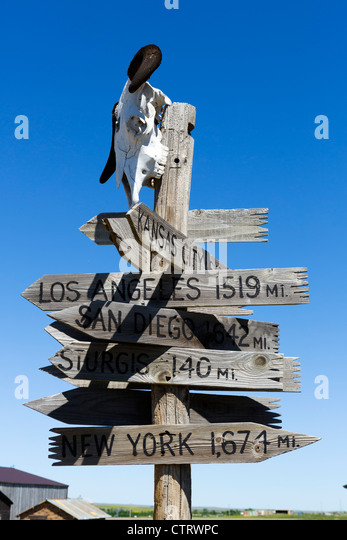 Signpost showing distances to major US cities in '1880 Town' western attraction in Murdo, South Dakota, - Stock-Bilder