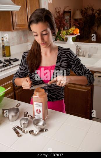 Teenage Girl In Kitchen Cooking Dark Lighting