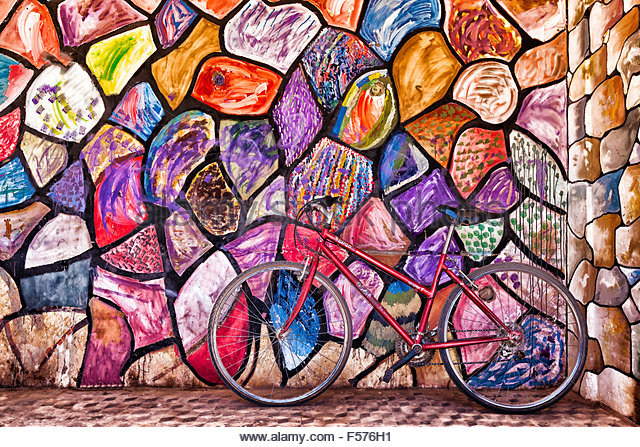 Red bicycle against colorful, abstract painted wall, Tamgroute, Morocco. - Stock Image