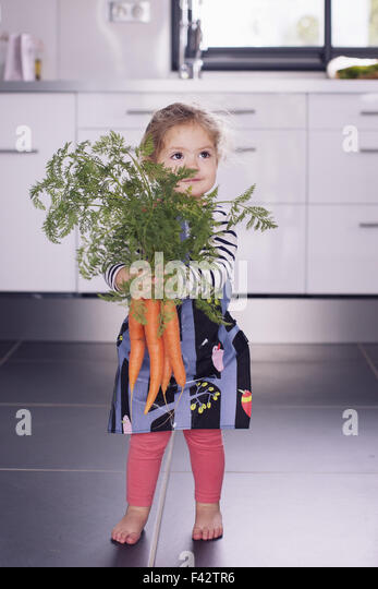 Little girl holding fresh carrots - Stock Image