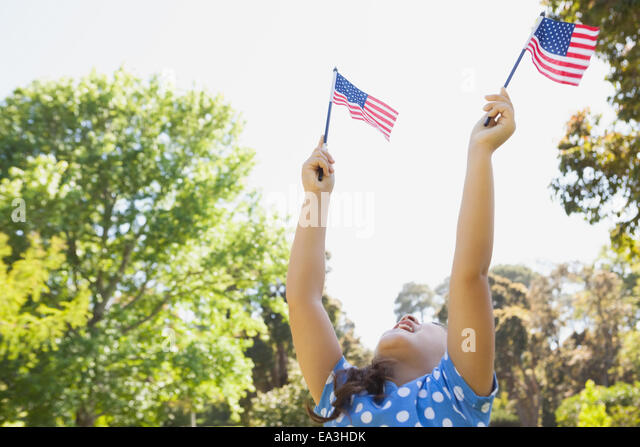 Girl holding up two American flags at park - Stock Image