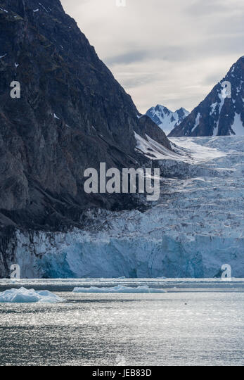 The edge of a glacier is covered with rock fragments fallen from the rock cliffs. - Stock Image