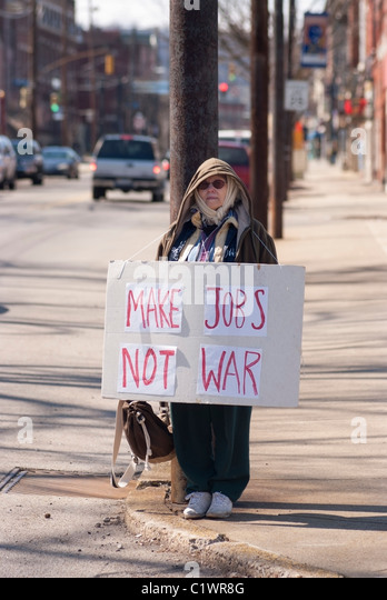 A 68-year-old Pittsburgh woman stands on the street before an Anti-War demonstration in Pittsburgh, PA. - Stock Image