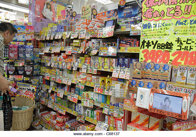 Japan Tokyo Shinjuku drugstore pharmacy kanji hiragana katakana characters Japanese and English for sale retail - Stock Image