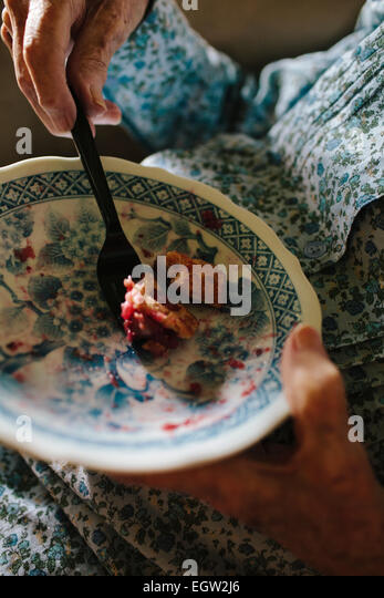 Close up of senior woman's hands eating pie. - Stock-Bilder