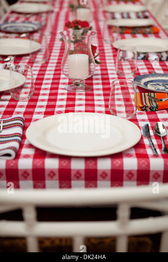 Place settings on red and white checkered tablecloth - Stock Image