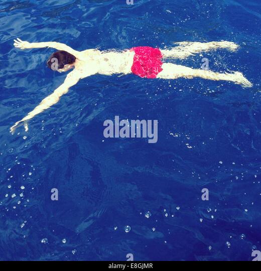 Man floating upside down  in blue water - Stock-Bilder