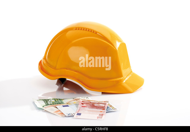 Hardhat and different Euro bank notes in foreground - Stock Image