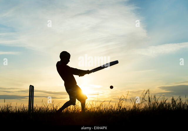 Silhouette of young boy playing cricket against a sunset background - Stock Image