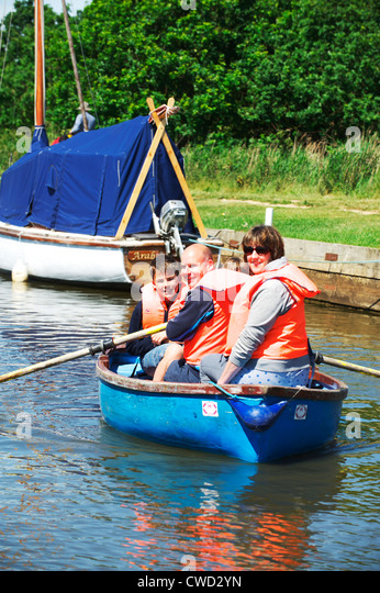 A Young family enjoy taking a rowing boat out on the Norfolk Broads while wearing life jackets - Stock Image