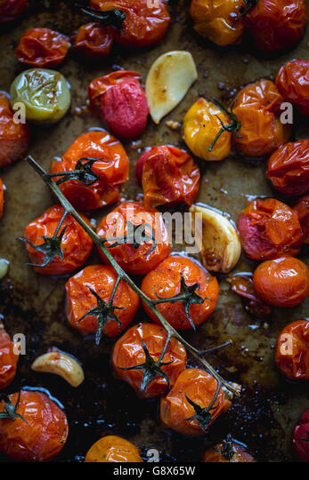 Freshly roasted tomatoes are photographed as soon as they get out of the oven. - Stock Image
