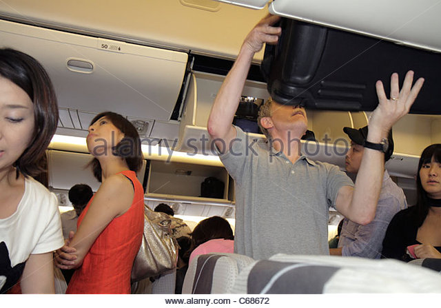 Tokyo Japan Haneda Airport Japan Airlines onboard commercial airliner passengers overhead luggage bins Asian woman - Stock Image