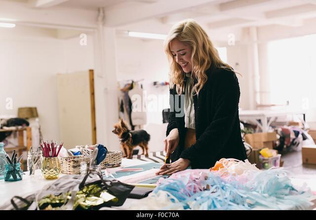 Female textile designer cutting textiles in design studio - Stock Image