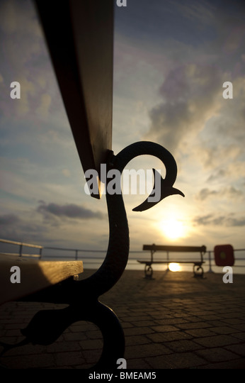 Silhouette of seaside benches at sunset, Aberystwyth Wales UK - Stock Image